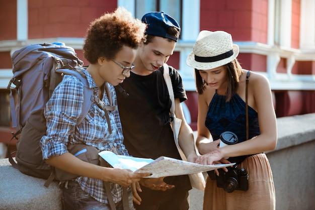Viaggiatori di amici con zaini sorridenti, guardando il percorso sulla mappa in strada. Foto Gratuite