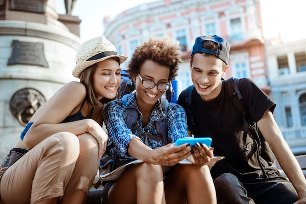 Friends travelers with backpacks smiling, making selfie, sitting near sight. Free Photo
