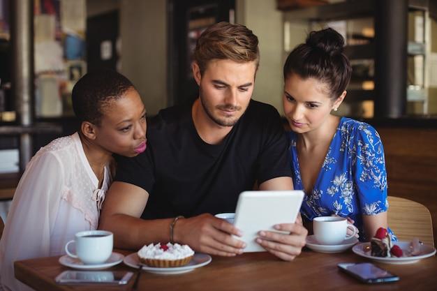 Друзья, использующие цифровой планшет во время завтрака Premium Фотографии