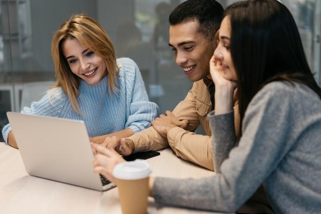 Друзья используют ноутбук, смотрят вебинар и обучающие курсы Premium Фотографии