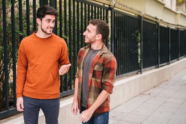 Friends walking talking at street Free Photo
