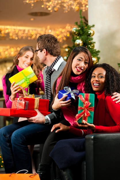 Friends With Christmas Presents And Bags In Mall Premium Photo