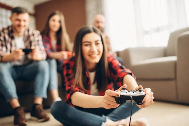 Друзья с джойстиками играют дома на телевизионной консоли Premium Фотографии