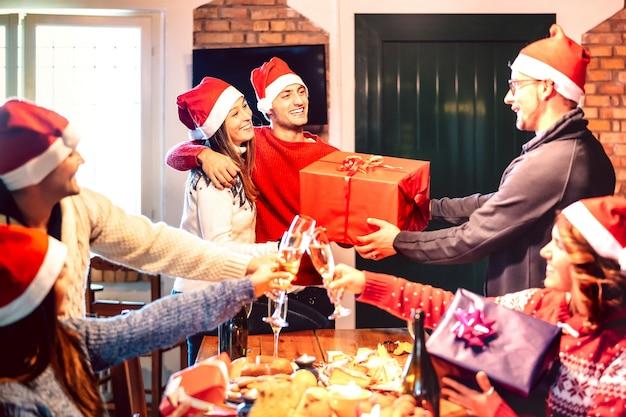 Друзья в новогодней шапке дарят друг другу рождественский подарок Premium Фотографии