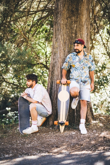 Friends with skateboards in forest Free Photo