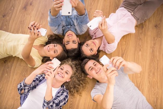 Friends with smartphones lying on floor in circle. Premium Photo