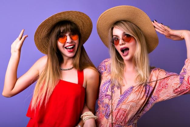 우정과 의사 소통 개념, 두 자매 최고의 잎 여자는 유행 여름 옷장과 일치하는 Colocar를 착용하고 카메라, Boho 안경, 보라색 배경에 포옹하고 보인다. 무료 사진