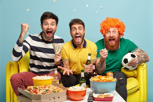友情、ゲーム、ギャンブル、レジャーの概念。感情的に興奮した3人の男性の友人が自宅のテレビでサッカーの試合を観戦し、拳を握りしめ、ゴール中に叫ぶ 無料写真