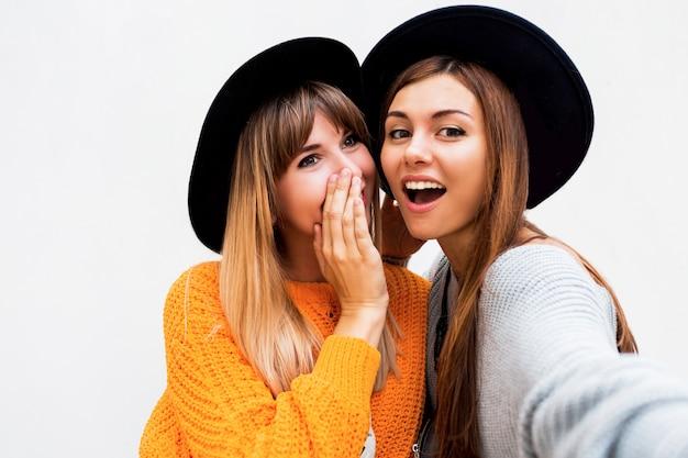 Концепция дружбы, счастья и людей. две улыбающиеся девушки шептались на белом Бесплатные Фотографии