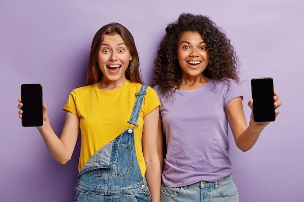 Дружба, технологии, рекламная концепция. два улыбающихся многонационального подростка стоят рядом, показывают смартфоны с макетами экранов для вашего текста Бесплатные Фотографии