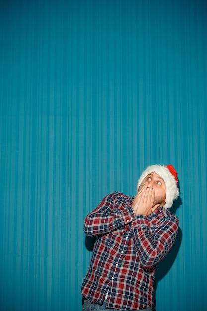 サンタの帽子をかぶっておびえたクリスマス男 無料写真