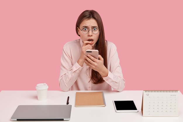 Frightened displeased woman holds mobile phone, has everything neatly arranged on table Free Photo