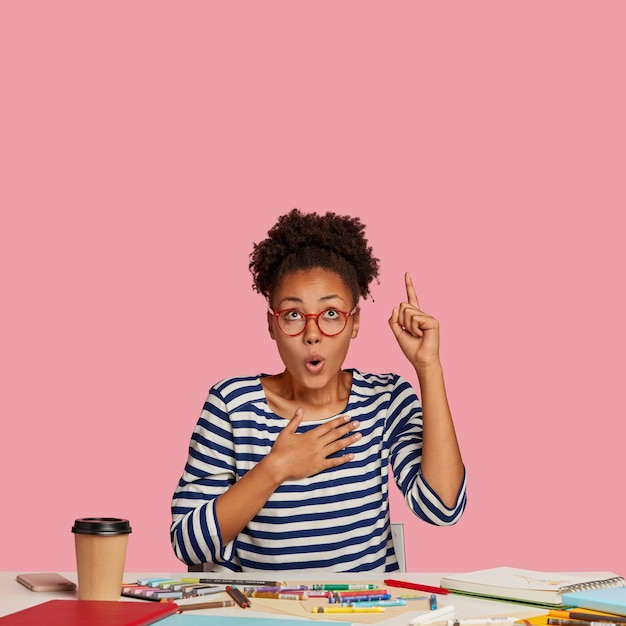 Frightened emotional dark skinned female designer raises index finger, keeps hand on breast, points upwards, notices unbelievable item, uses notebook, caryons for making sketch sits in coworking space Free Photo