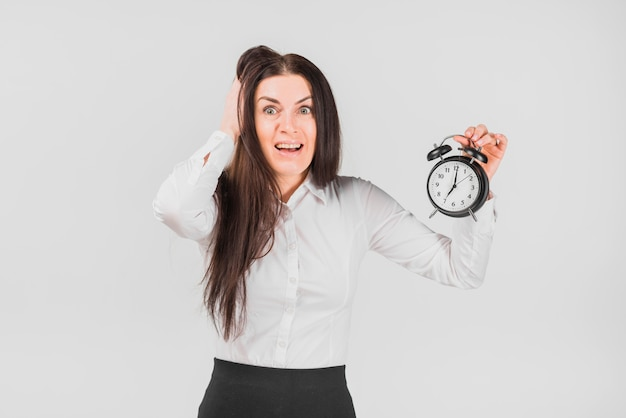 Frightened female holding hair and alarm clock Free Photo