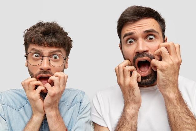 おびえた二人の男は表情を怖がらせ、神経質に見え、道路でのひどい事故に気づき、ひどいことに反応する 無料写真