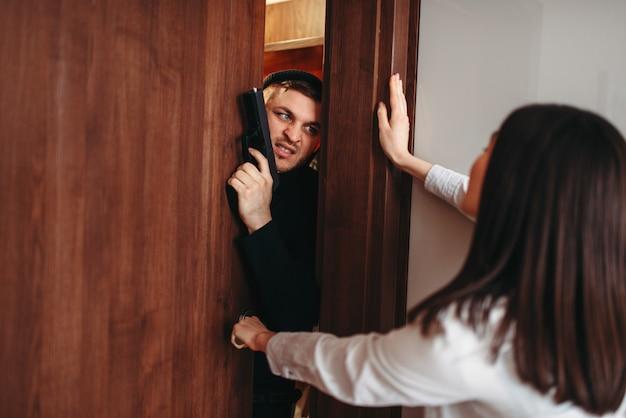 문을 닫으려는 겁에 질린 여성, 손에 총을 든 검은 옷을 입은 살인범이 아파트를 뚫고 싶어합니다. 집에서 강도 프리미엄 사진