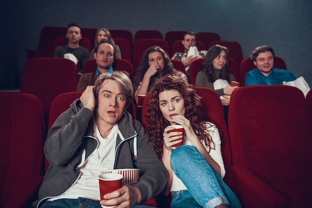 Frightened young couple watching thriller at cinema. Premium Photo