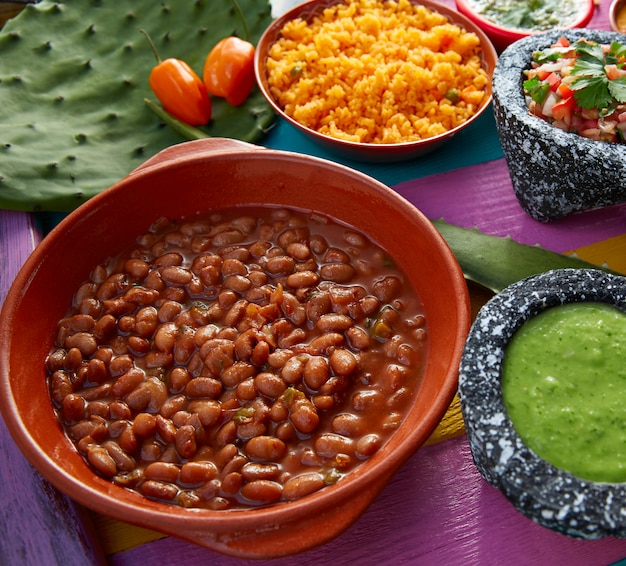 Frijoles mexican beans with rice and sauces Premium Photo