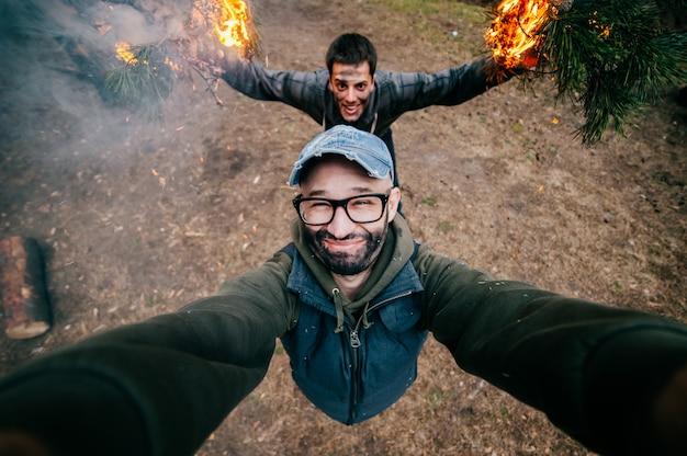 友達は自分撮りをします。クレイジー面白い男の子がぐちゃぐちゃ。自然で遊んで、火でだましている男性。森でエッチな奇妙な奇妙な珍しい若い男が汚い顔で狂ったパーティー。火傷、炎、煙。 Premium写真