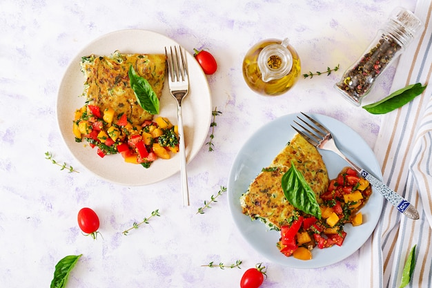 Frittata with zucchini, cheese, basil and salsa from tomatoes.  italian omelette. Premium Photo