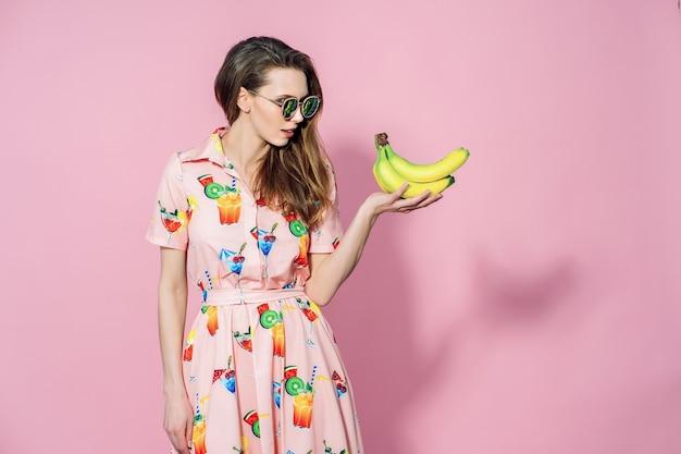 Красивая женщина в красочном платье с напечатанными friuts представляя с бананами Premium Фотографии