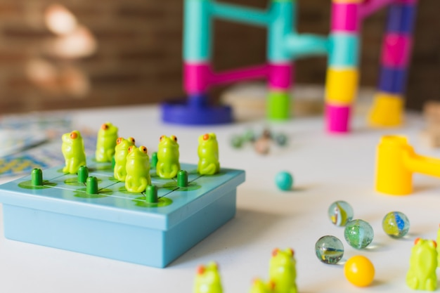 Frog game with marbles on table Free Photo