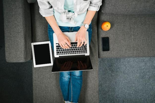Desde arriba de la computadora portátil de navegación en el sofá Foto gratis