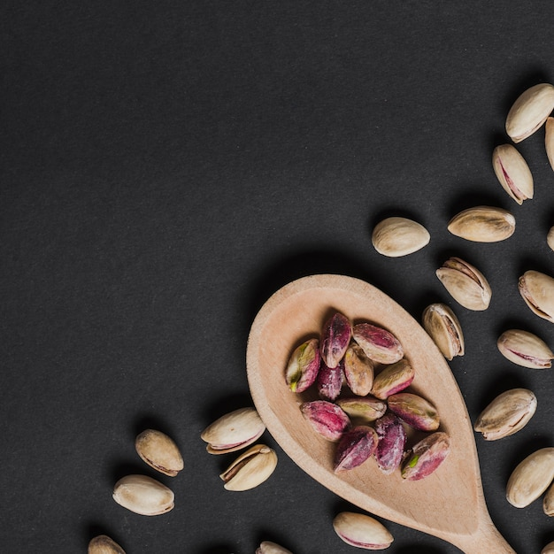 From above spoon with peeled pistachios