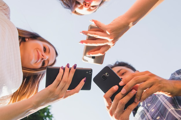 From below view of teens with smartphones Free Photo