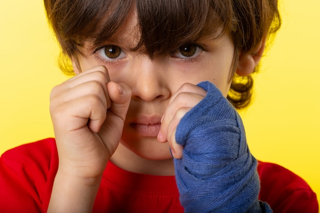 A front close up view cute child in red t-shirt posing in boxing on the yellow wall Free Photo