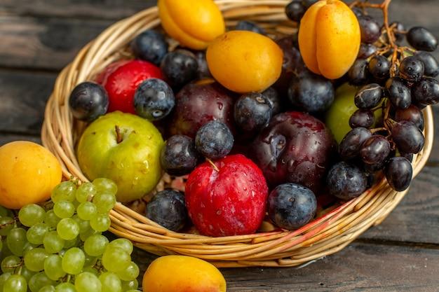 茶色の素朴なデスクフルーツにブドウのアプリコットプラムなどのまろやかなフルーツと酸味のあるフルーツが入ったフロントビューバスケット 無料写真