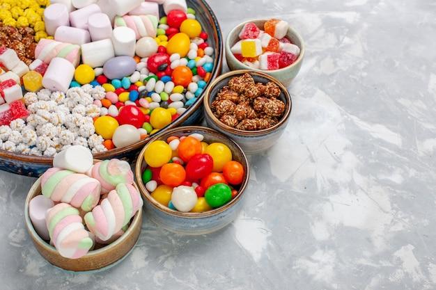 白い机の上にマシュマロと正面のクローズビューキャンディー組成物の異なる色のキャンディー 無料写真