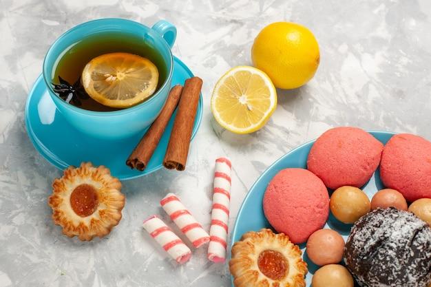 Vista ravvicinata anteriore tazza di tè con macarons francesi biscotti e torte sulla parete bianca luce zucchero biscotto torta dolce caramella biscotto Foto Gratuite
