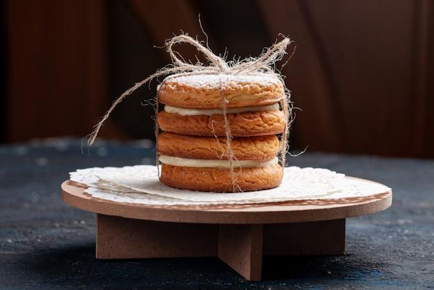 Вид спереди крупным планом вкусные сэндвич-печенья, завязанные вкусняшками на темно-синем торте на столе Бесплатные Фотографии