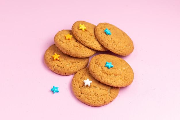 Vista ravvicinata anteriore deliziosi biscotti dolci al forno rivestiti sullo sfondo rosa zucchero dolce biscotto cuocere il tè Foto Gratuite