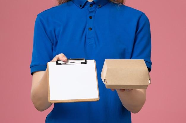 ピンクの壁にメモ帳付きの小さな配達食品パッケージを保持している青い制服と岬の正面の女性の宅配便、仕事配達サービスの従業員の仕事 無料写真