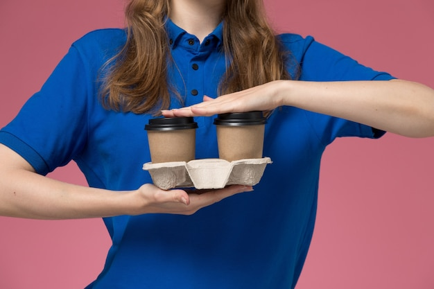 ピンクのデスクサービス制服配達会社の仕事に茶色の配達コーヒーカップを保持している青い制服を着た正面の女性の宅配便 無料写真