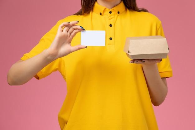 黄色の制服と薄ピンクの壁に小さな配達食品パッケージとカードを保持している岬の正面のクローズビュー女性宅配便、サービス制服配達会社の仕事 無料写真