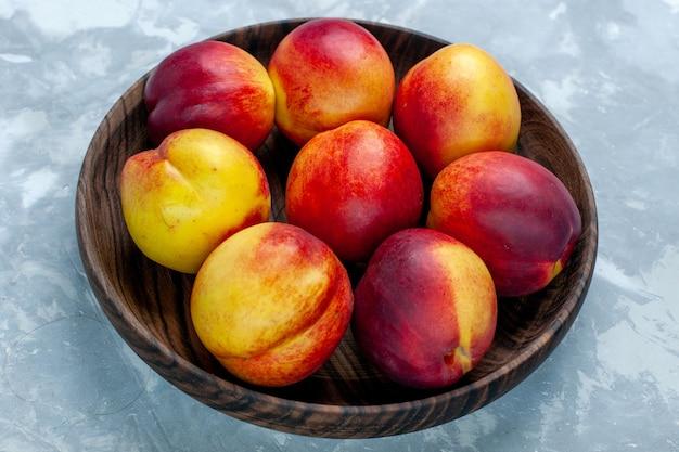 Vista ravvicinata frontale pesche fresche frutta pastosa e gustosa all'interno del piatto marrone sullo scrittorio bianco-chiaro Foto Gratuite
