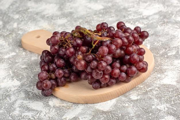 正面のクローズビュー新鮮な赤ブドウのまろやかでジューシーなフルーツが薄白の表面に 無料写真