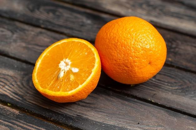 Vista ravvicinata anteriore arance fresche acide succose e pastose isolate su fondo rustico marrone frutta agrumi tropico fresco succo acido Foto Gratuite