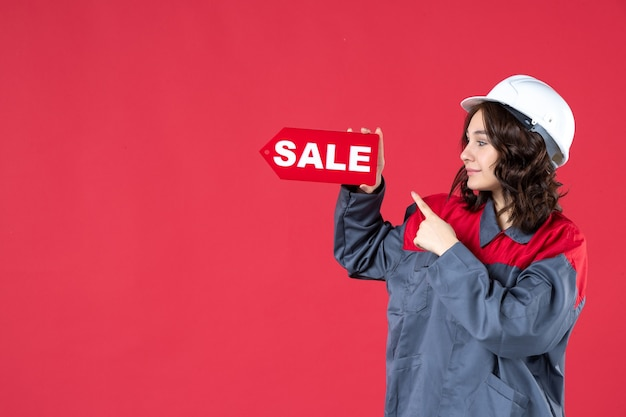 Vista frontale ravvicinata della lavoratrice felice in uniforme che indossa elmetto e che indica l'icona di vendita sulla parete rossa isolata Foto Gratuite