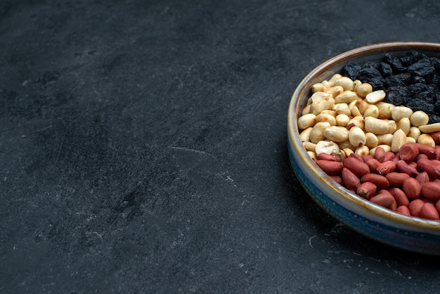 Front close view hazelnuts and raisins and other nuts on the dark-grey surface Free Photo