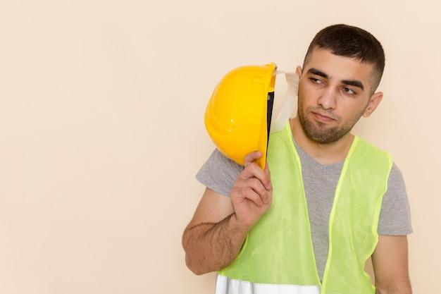 Costruttore maschio di vista ravvicinata anteriore che tiene casco protettivo giallo su sfondo chiaro Foto Gratuite