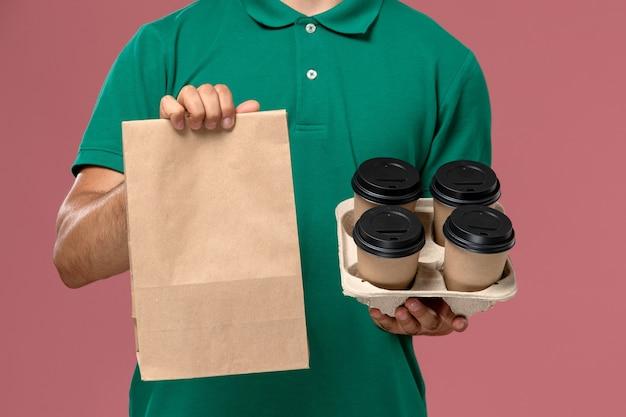 ピンクの机の上に茶色のコーヒーカップと食品パッケージを保持している緑の制服を着た正面の拡大図男性宅配便 無料写真