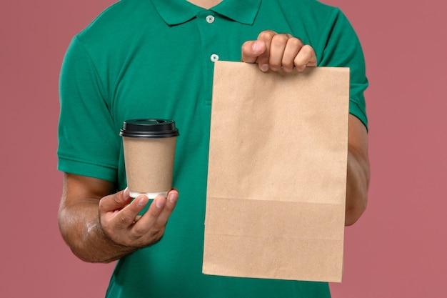 Вид спереди крупным планом мужской курьер в зеленой форме, держащий чашку кофе и пакет с едой на светло-розовом фоне Бесплатные Фотографии