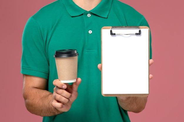 Крупным планом вид спереди мужчина-курьер в зеленой форме, держащий чашку кофе и блокнот на светло-розовом столе Бесплатные Фотографии