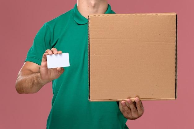 ピンクの背景に白いカードとフードボックスを保持している緑の制服を着た正面の拡大図男性宅配便 無料写真
