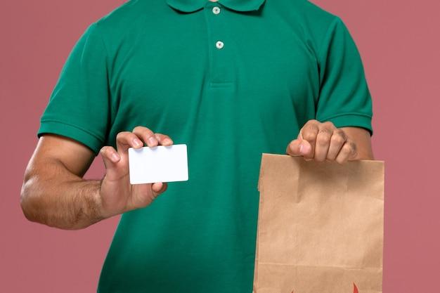 ピンクの背景に食品パッケージとカードを保持している緑の制服を着た正面の拡大図男性宅配便 無料写真