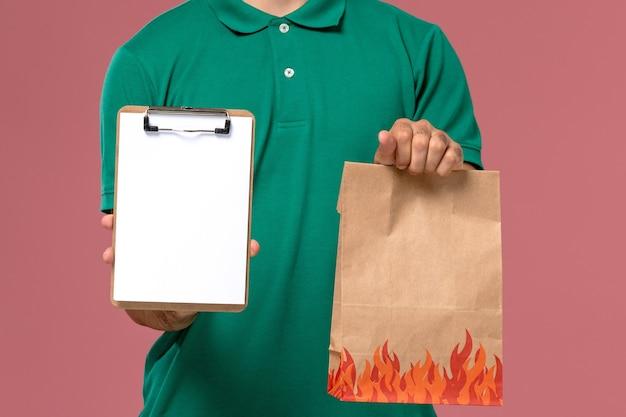 淡いピンクの背景に食品パッケージとメモ帳を保持している緑の制服を着た正面の拡大図男性宅配便 無料写真